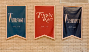 Flags with Reinhold Residential apartment property names hanging in the MetroFit basketball court