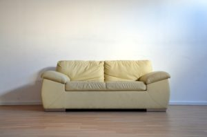 yellow leather used sofa in an empty room