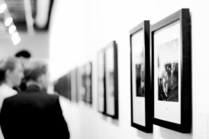 people viewing photographs at an art exhibit