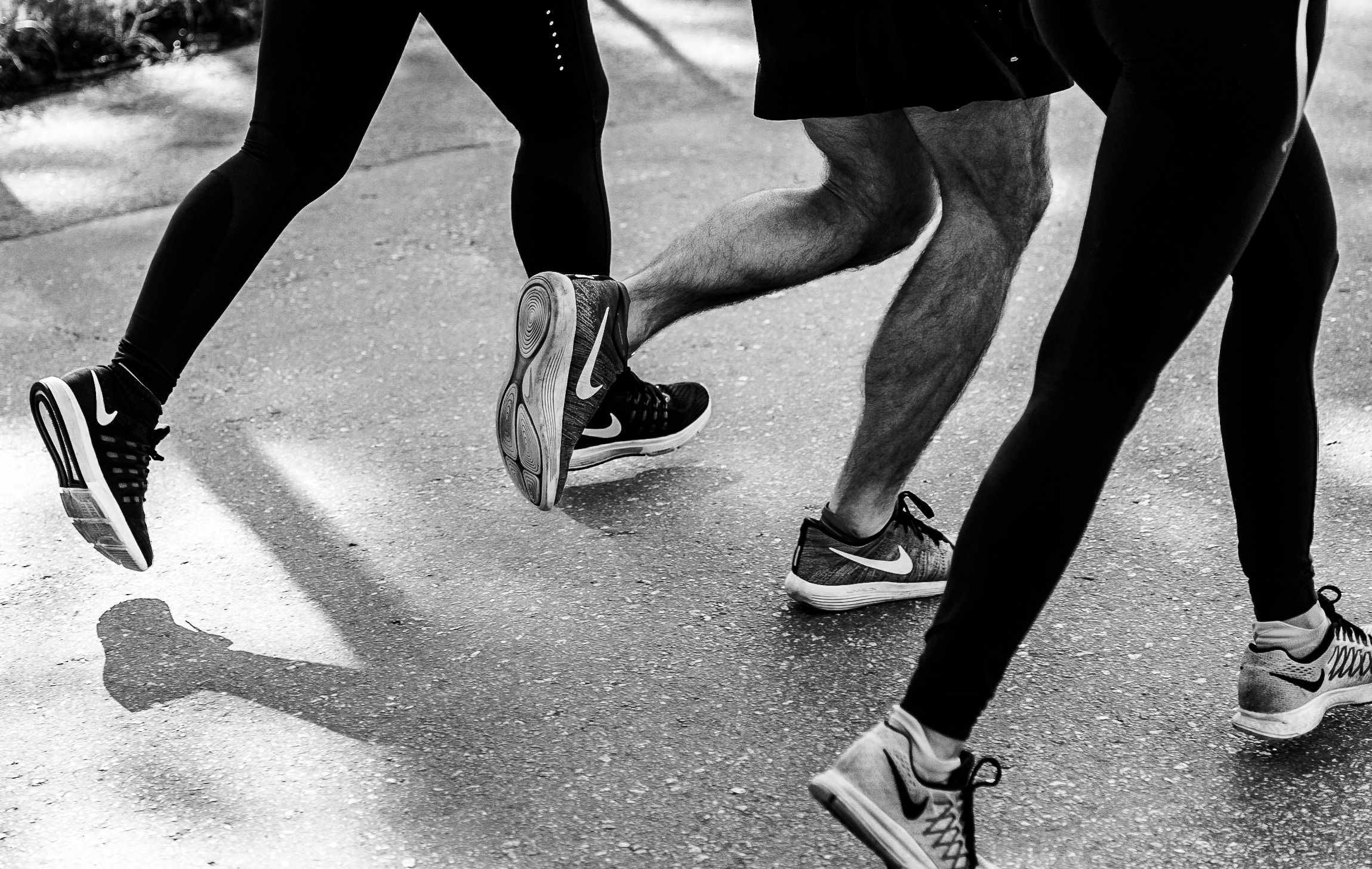 legs and feet of three runners on sidewalk