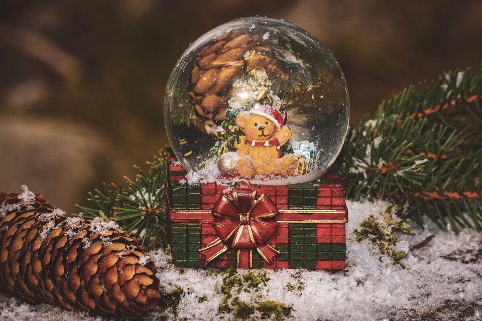 a teddy bear inside of a holiday snow globe on top of a present