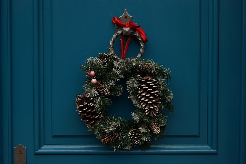 brown and green holiday wreath on a dark blue door