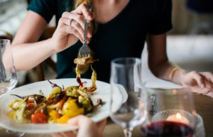 Woman dining on a roasted vegetable plate and red wine at an Italian restaurant
