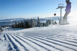Winter ski slope with a chair lift and snowboarder