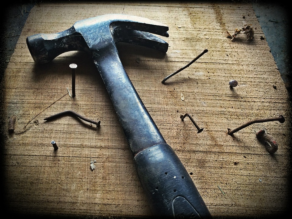 close up of a hammer and various nails in a wooden board