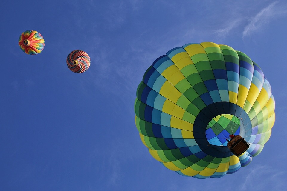 Three hot air balloons soaring in a cloudless blue sky