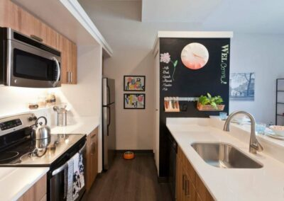 Old City apartment kitchen with stainless steel appliances, quartz countertops, and breakfast bar